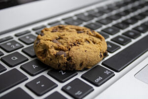 A chocolate chip cookie rests on a computer keyboard.