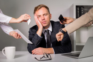 A tired man in a suit sits at his desk, resting his head against his hand, as four coworker hands show tasks that need his attention by holding out an envelope, phone, and watch respectively.